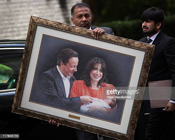 An aid to President Zardari Of Pakistan carries a painting of British Prime Minister David Cameron with his wife Samantha holding their newborn...