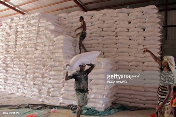 An aid worker carries a sack of flour in the northern province of Hajjah on September 25 as Yemenis displaced from the port city of Hodeidah receive...