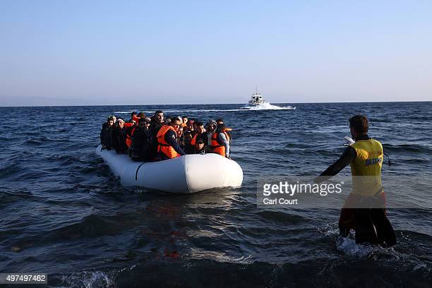 An aid worker gestures at a migrant boat as it approaches shore after making the crossing from Turkey to the Greek island of Lesbos on November 17...