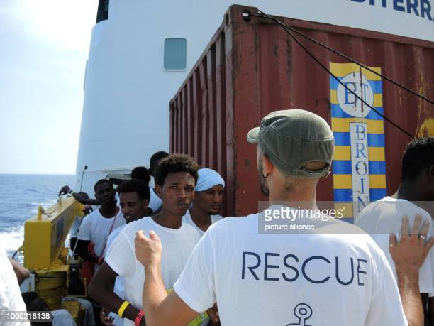 An aid worker on the rescue ship 'Aquarius' directs migrants who have newly arrived on the boat in the Mediterranean Sea 28 June 2017 The...
