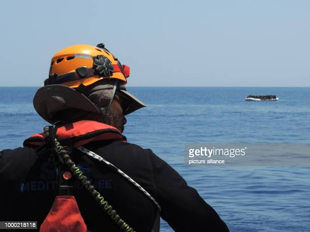 An aid worker on the rescue ship 'Aquarius' spots a small migrant boat in the Mediterranean Sea 27 June 2017 The humanitarian aid organisation...