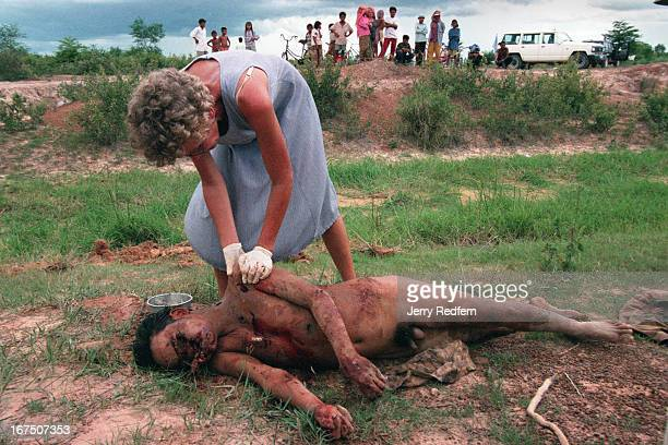 An aid worker performs a field autopsy on the body of a man left in a shallow grave just outside Phnom Penh. Nearby residents said that he and...