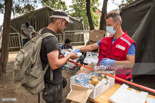"""An aid worker with the Serbian Red Cross distributes water and hygiene items to Syrian and Afghan refugees at the so-called """"one stop"""" camp set up by..."""