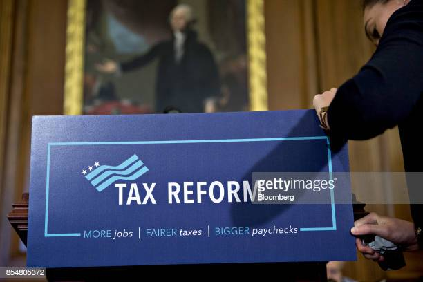 An aide from the office of US House Speaker Paul Ryan removes a 'Tax Reform' sign from a podium after a news conference on a unified tax reform...