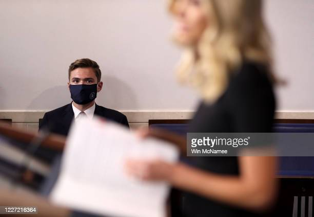 An aide listens as White House press secretary Kayleigh McEnany answers questions during the daily briefing at the White House on May 26, 2020 in...