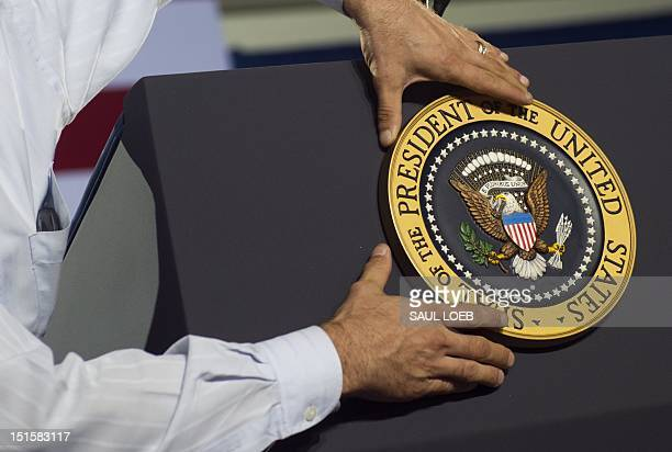 An aide places the Presidential seal on the podium prior to US President Barack Obama speaking during a campaign event at Kissimmee Civic Center in...