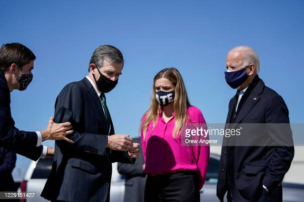 An aide pulls back North Carolina Governor Roy Cooper to better socially distance as he speaks with Democratic presidential Joe Biden and his...