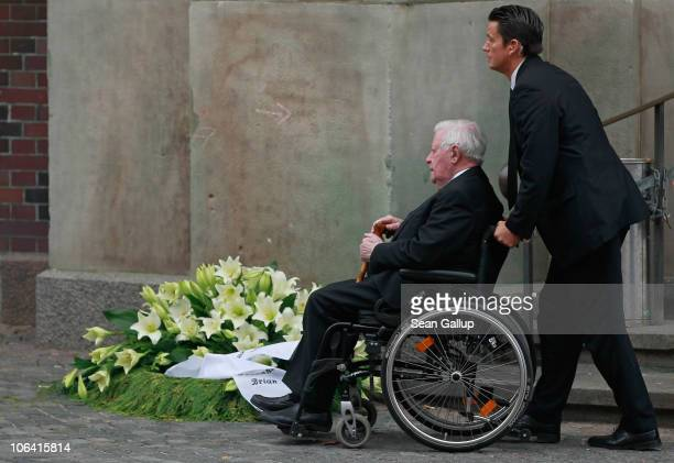 An aide pushes former German Chancellor Helmut Schmidt past a funeral wreath following the memorial service for Schmidt's recently deceased wife Loki...