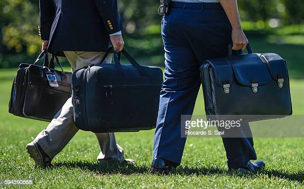 An aide to Barack Obama carries the 'football' a secured briefcase that holds the nuclear codes on August 23 2016 in Washington DC