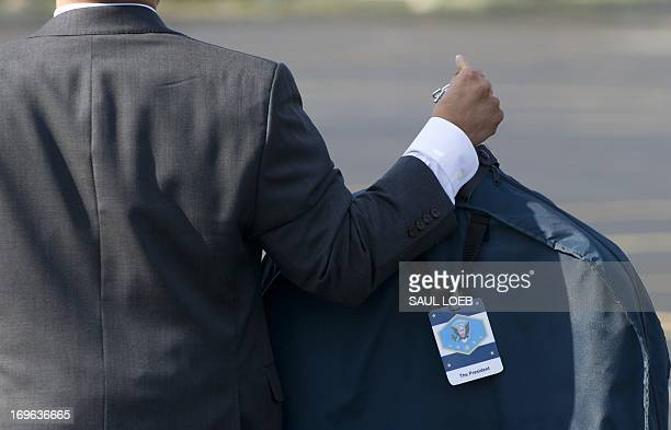 An aide to US President Barack Obama carries a suit bag upon arrival in Chicago Illinois May 29 2013 Obama is traveling to attend Democratic...