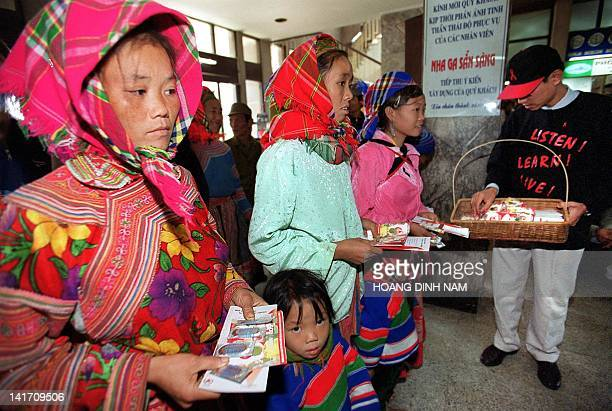 An AIDS activist distributes AIDS leaflets and condoms to H'mong hill tribe women while they wait for their train at Hanoi railway station 30...