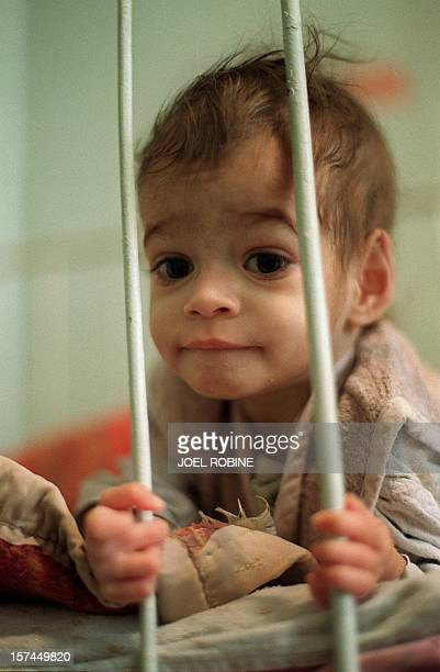 An AIDS infected child looks through the bars of his hospital bed in the pediatric ward of the Victor Babes hospital 07 February 1990 in Bucharest