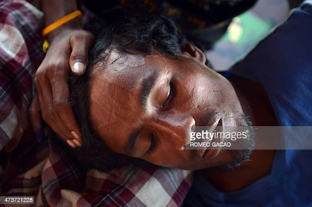An ailing rescued migrant from Bangladesh lies in a medical tent at the confinement area in the fishing port of Kuala Langsa in Aceh province on May...