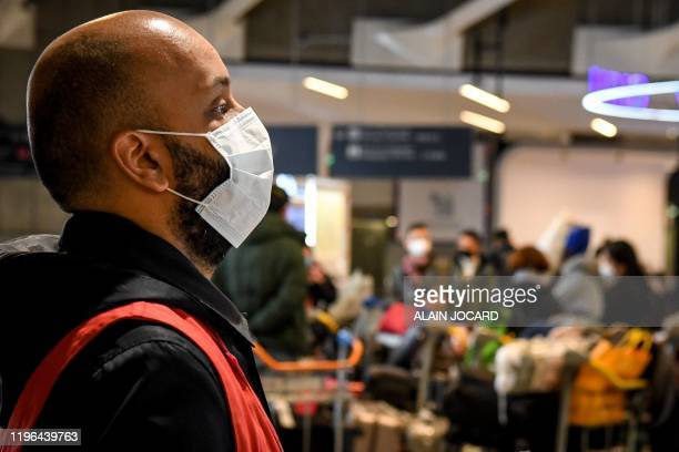 An aiport worker , wearing a protective face mask, stands in front of passengers coming from China, at the arrival Terminal in Charles De Gaulle...