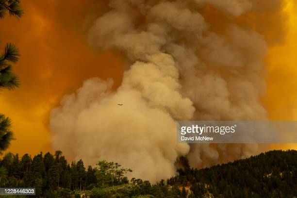 An air attack plane flies by the plume as the Bobcat Fire advances in the Angeles National Forest on September 10, 2020 north of Monrovia,...