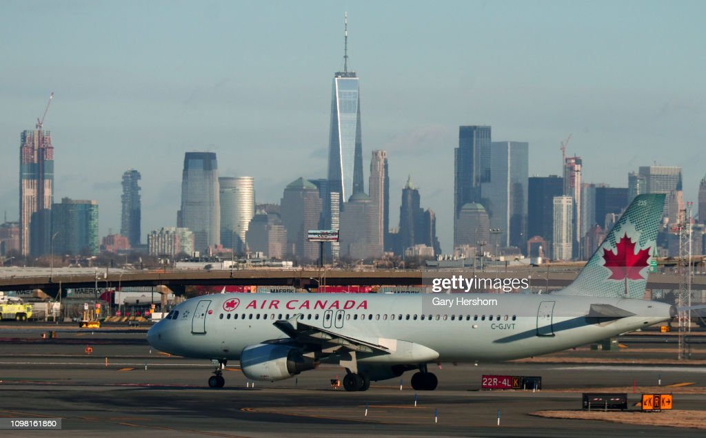 An Air Canada airplane passes by the skyline of lower