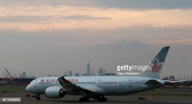An Air Canada airplane passes by the skyline of lower Manhattan in New York City as it taxis to a runway at Newark Liberty Airport on July 20 2017 in...