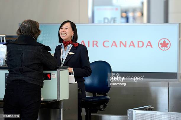 An Air Canada employee helps a traveler checkin at Pearson International Airport in Toronto Ontario Canada on Wednesday Feb 6 2013 Air Canada the...