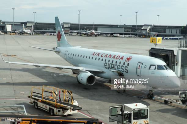 An Air Canada express jet Embraer sits at gate at MontréalPierre Elliott Trudeau International Airport on July 16 2019