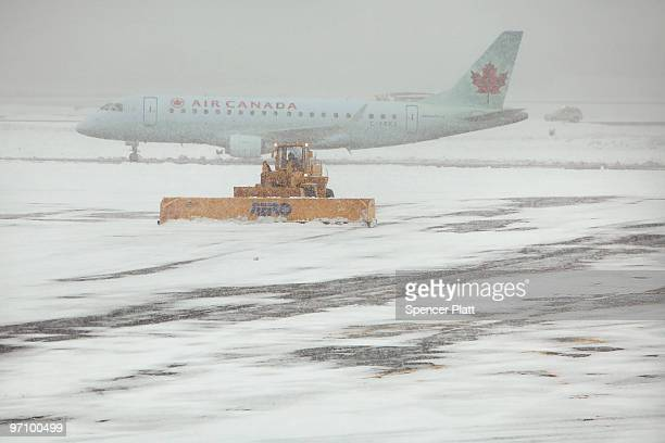 An Air Canada plane is viewed on the tarmac at La Guardia Airport during a snow storm on February 26 2010 in the Queens borough of New York City The...