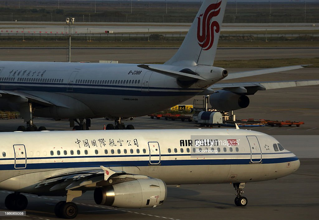 An Air China Ltd. aircraft taxies past another Air China aircraft at Shanghai Pudong International Airport in Shanghai, China, on Saturday, Oct. 26, 2013. Airline profits worldwide in 2013 will be 7.9 percent smaller than estimated at $11.7 billion amid sluggish travel demand and rising oil prices tied to the Syria crisis, the International Air Transport Association said last month. Photographer: Tomohiro Ohsumi/Bloomberg via Getty Images