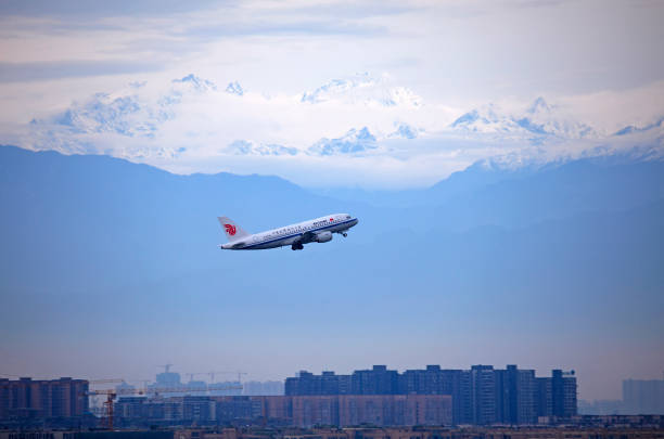 CHN: Planes Flies In Front Of Snowcapped Mountain In Sichuan