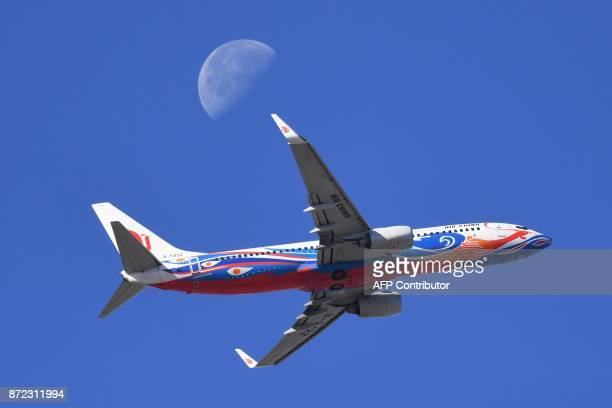 An Air China plane flies in front of the moon as it takes off from Beijing airport on November 10 2017 / AFP PHOTO / GREG BAKER