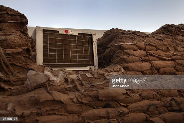 An air conditioner, protected by deteriorating sand bags, cools trailer housing for U.S. Embassy staff in the Green Zone September 3, 2007 in...