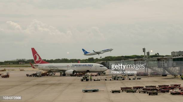 An Air Europa airplane takes off while airport personnel load luggage into a Turkish Airlines airplane sitting on the tarmac at Terminal 1 of...