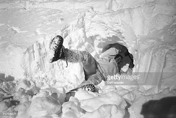 An Air Force Academy cadet lies on his side as he uses a shovel to dig a snow cave near Loveland Pass Colorado February 4 1963