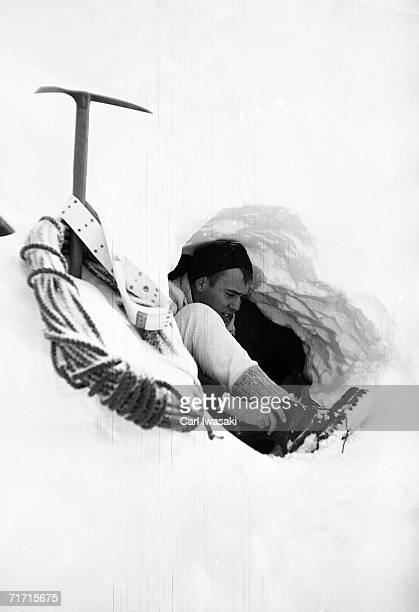 An Air Force Academy cadet pulls on one of his boots in the entrance to a manmade snow cave near Loveland Pass Colorado February 4 1963