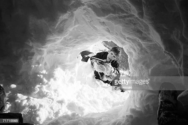 An Air Force Academy cadet uses a shovel to dig a snow cave near Loveland Pass Colorado February 4 1963
