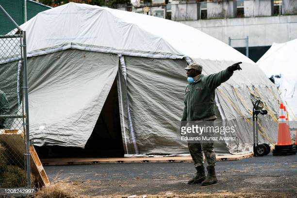 An Air Force member gives instructions as workers and members of the National Guard build a makeshift morgue outside of Bellevue Hospital on March 25...