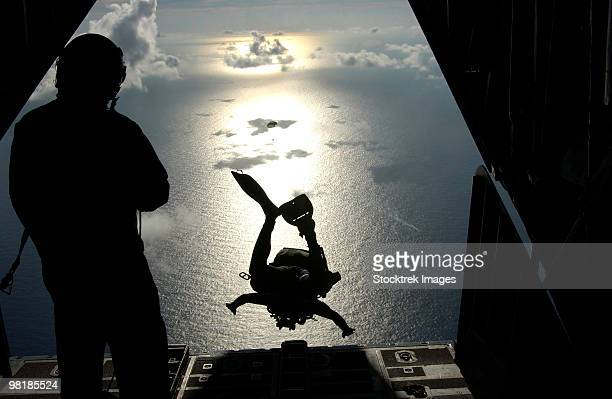 An Air Force pararescueman jumps out of the back of an HC-130 Hercules.
