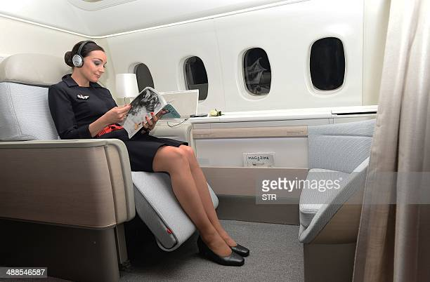 An Air France attendant shows off the airline's 'haute couture' suite featuring a seat that reclines into a bed stretching 201 metres long and 77...