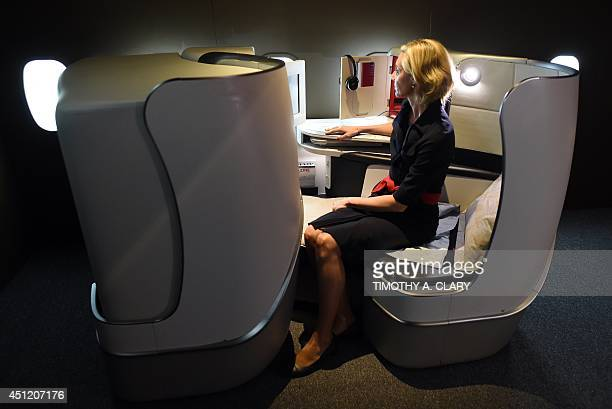 An Air France flight attendant tries out the new business class seating at the new Air France Exhibition called 'Air Francefrance is in the Air' in...