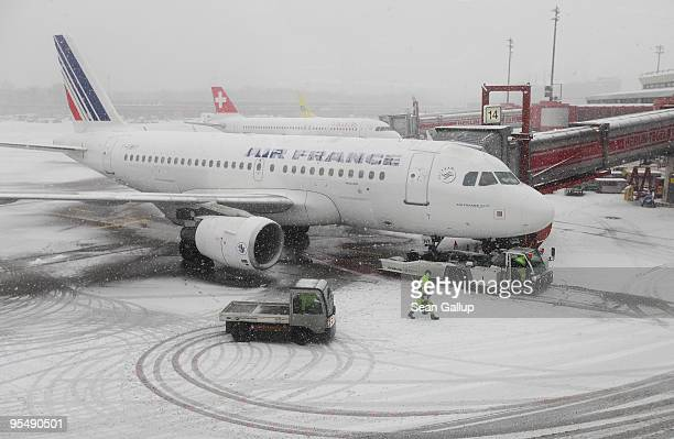 An Air France passenger jet stands at a gate covered in snow at Tegel Airport on December 30 2009 in Berlin Germany Temeperatures in the German...