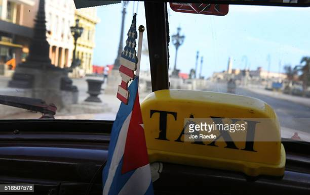 An air freshener in the colors of the American flag sits above a Cuban flag in a taxi as Cuba prepares for the visit of US president Barack Obama on...