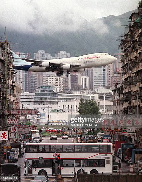 An Air Hong Kong plane comes in for landing over the crowded landscape of housing blocks near Kai Tak airport 05 July The cramped saturated urban...