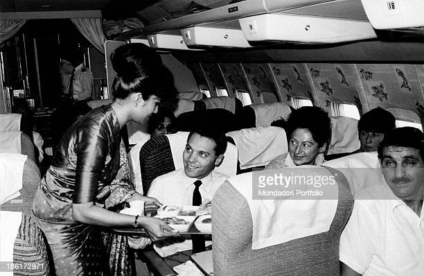 An air hostess in a sari serves breakfast to Italian photographer Angelo Cozzi during the flight to Bangkok where the famous photographer will shoot...