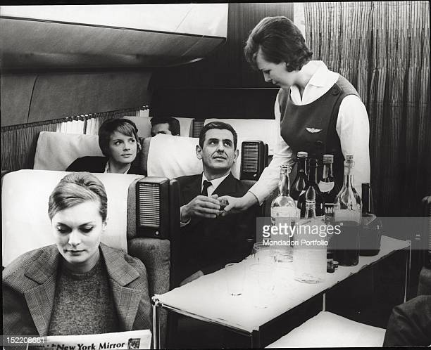 An air hostess offering a drink to the passengers on board plane 1960s