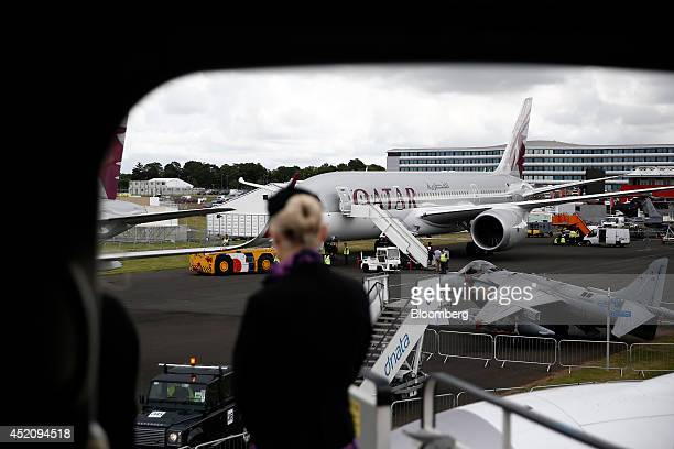 An air hostess stands on the access stairs leading to a Boeing 7879 Dreamliner aircraft produced by Boeing Co as she looks towards another Boeing 787...