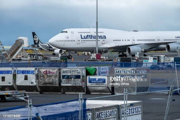 An Air New Zealand domestic flight passes behind the Lufthansa Boeing 747400 which arrived at 7am at Auckland International Airport to pick up German...