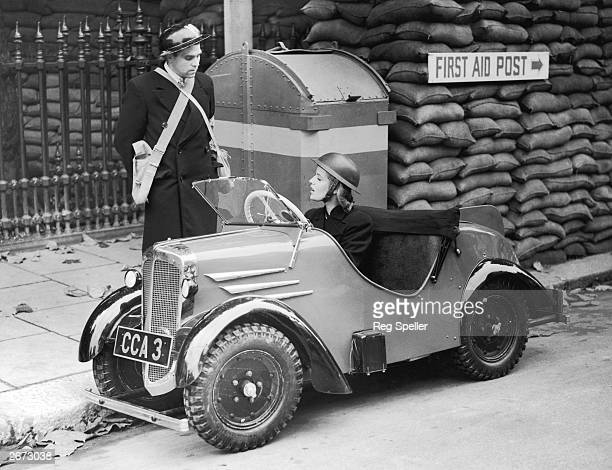 An air raid warden arrives at a shelter in a Rytecraft midget car