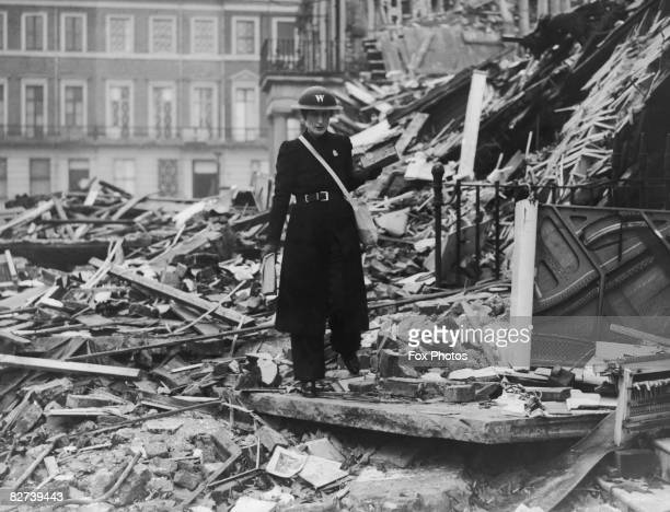 An air raid warden clambers through the ruins of a building after a World War II air raid on London 20th November 1940