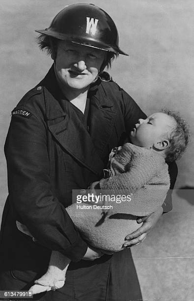 An air raid warden holds a sleeping baby at a rest center that houses children left homeless or orphaned by air raids | Location LCC Rest Centre...