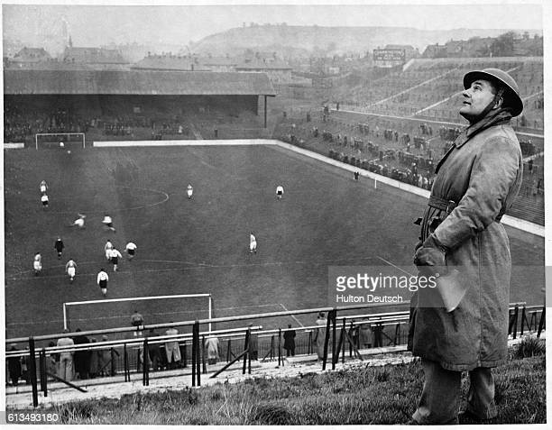 An air raid warden on the lookout for enemy planes at a football match between Charlton and Arsenal 1940