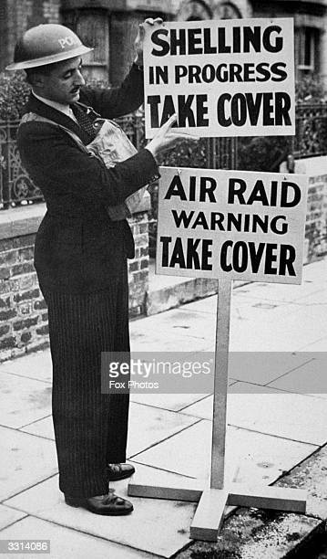 An air raid warden putting up signs drawing attention to the dangers from air raids and from shelling