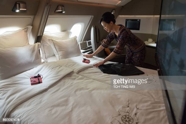 An air stewardess arranges bedsheets of a double bed in a suite of Singapore Airlines' new Airbus A380 during a tour of the plane at Changi Airport...