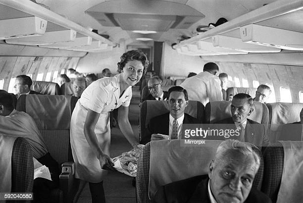 An air stewardess serving food to passengers on board a Qantas Boeing 707 plane at London airport 7th August 1959